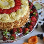 Vanilla cake with strawberries and pineapple with fruits laying around