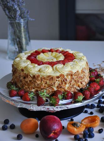 Vanilla cake with strawberries and pineapple decorated with pastry cream, strawberries, pineapple and almonds on a cake stand with fruit around