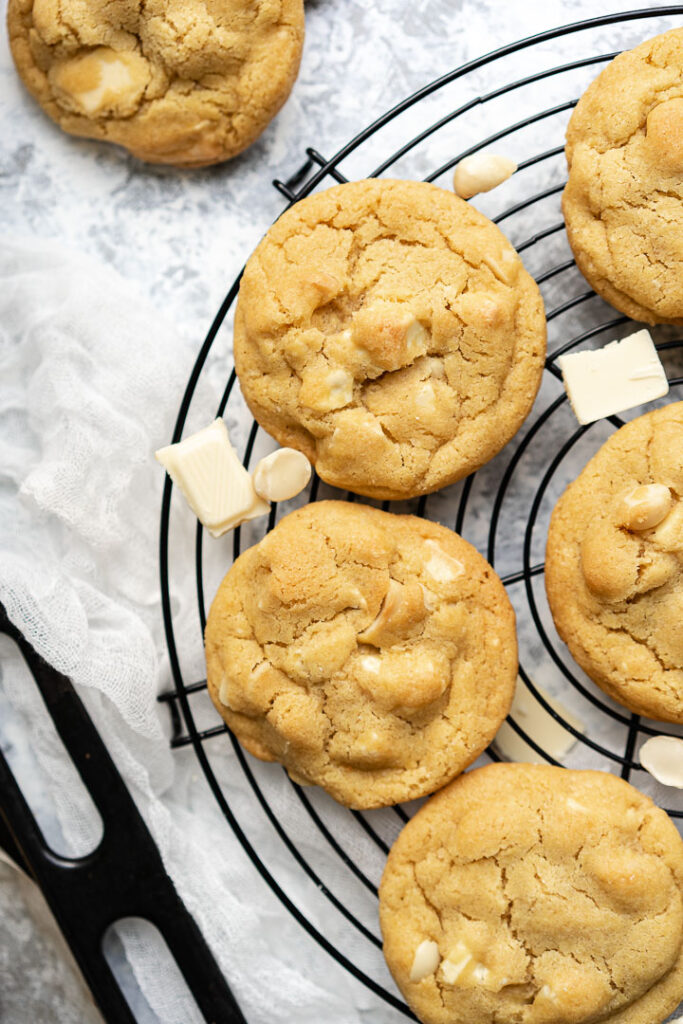 white chocolate macadamia cookies on a black rack and a black baking tray on the left