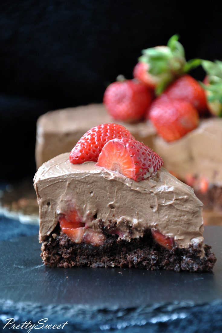 A piece of vegan chocolate mousse cake with strawberries