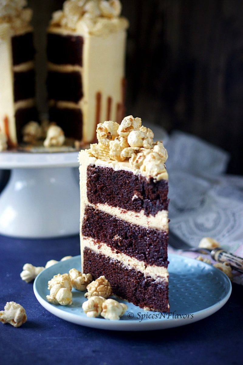 cut slice of eggless chocolate caramel cake standing tall showing the height of the cake along with the textures