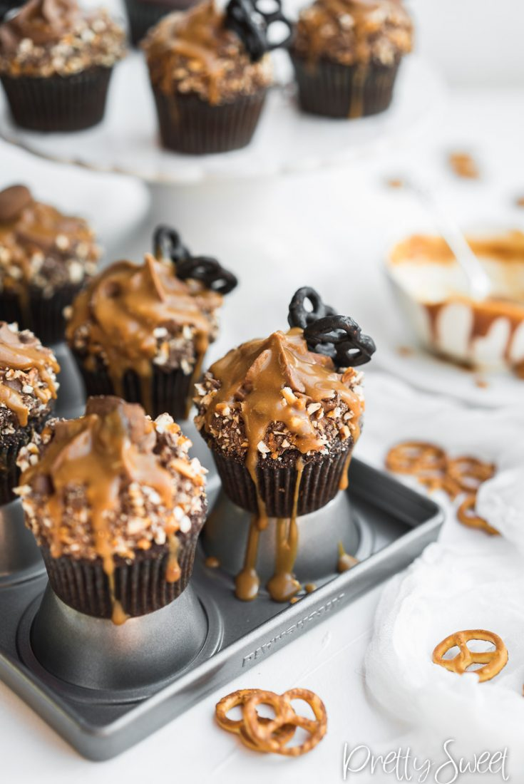 Salted Caramel filled Chocolate Cupcakes with whipped milk chocolate ganache and chocolate butterfly pretzels on a cupcake tin