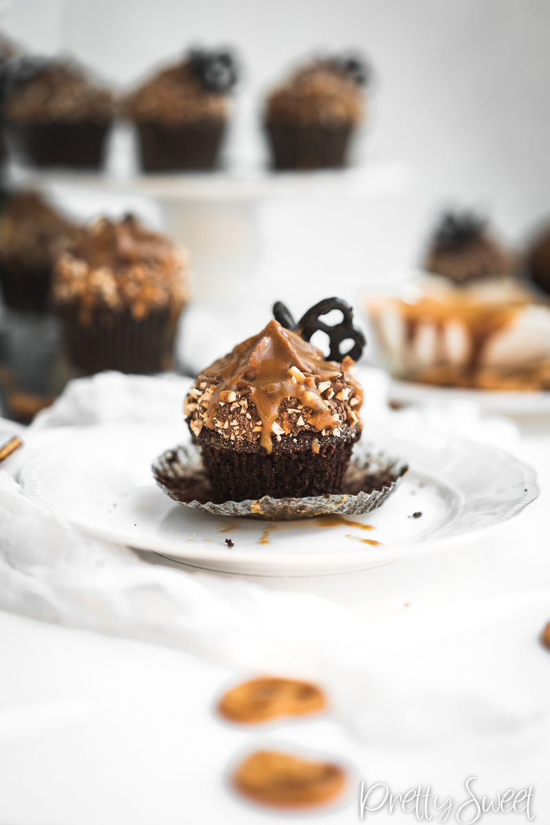 Salted Caramel filled Chocolate Cupcakes with whipped milk chocolate ganache and chocolate butterfly pretzels on a plate