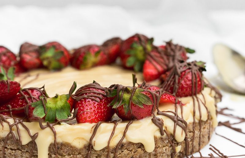 A cut piece of a protein cheesecake with straberries and drizzeled chocolate