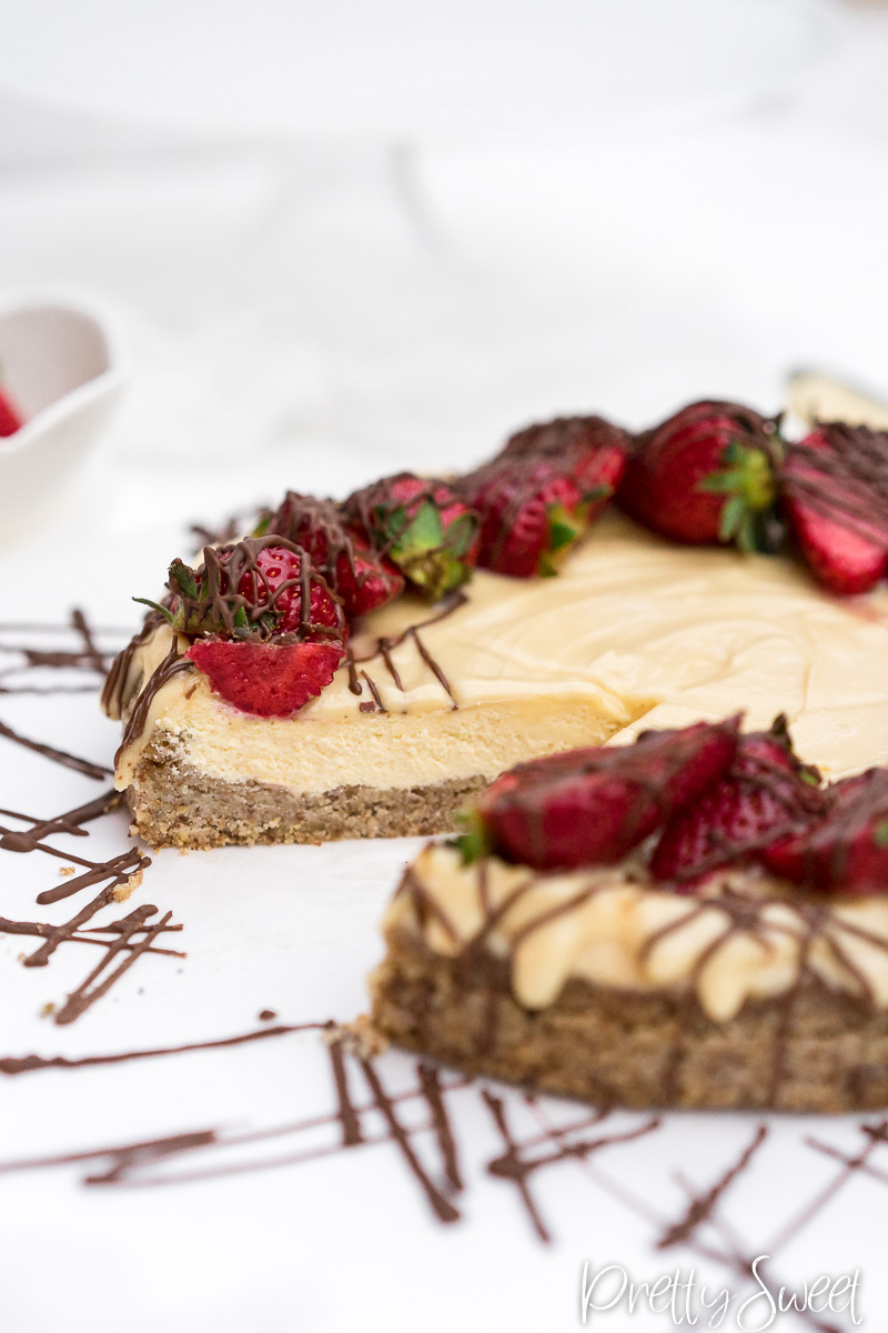 Protein cheesecake with straberries and drizzeled chocolate with a missing piece
