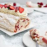 Sliced meringue roulade with strawberry rhubarb and mascarpone on a serving plate from the side
