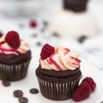 Raspberry chocolate cupcakes with cream cheese frosting topped with raspberries on a plate
