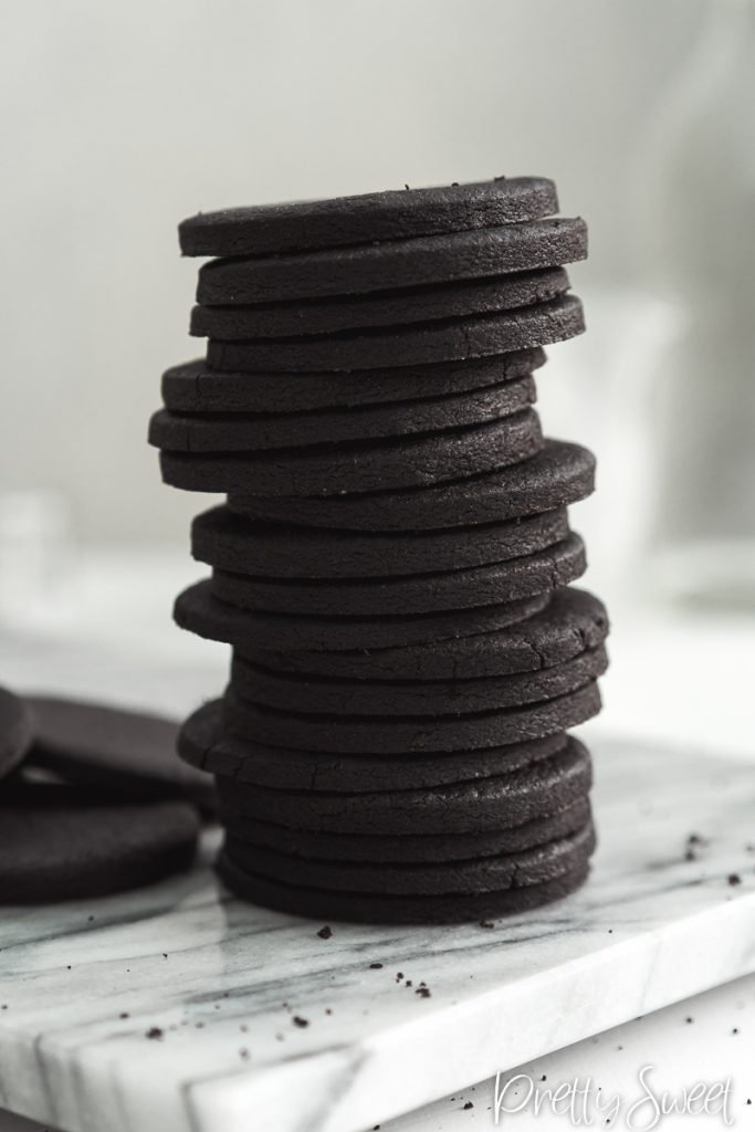 Round black cocoa shortbread cookies in a tall stack