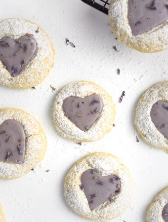 Close up of a lemon thumbprint cookie with a lavender ganache