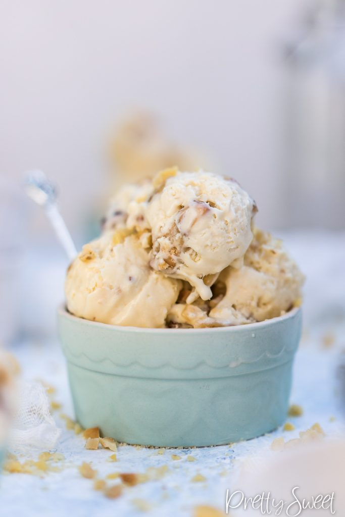 close up of scoops of no-churn vanilla ice cream with bits of macadamia nut brittle in a blue ramekin with a little spoon