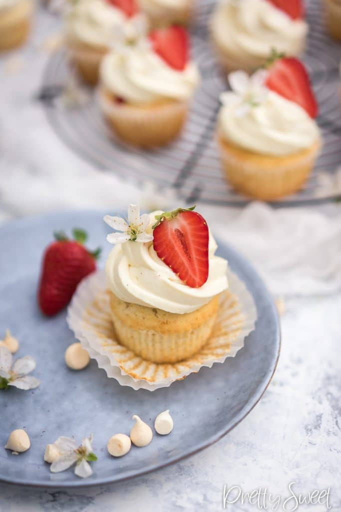 white cupcake with strawberry filling and mascarpone frosting swirl on a blue plate