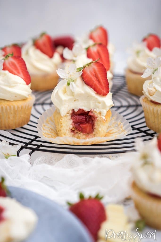 Bitten white cupcake with strawberry filling and white chocolate mascarpone frosting