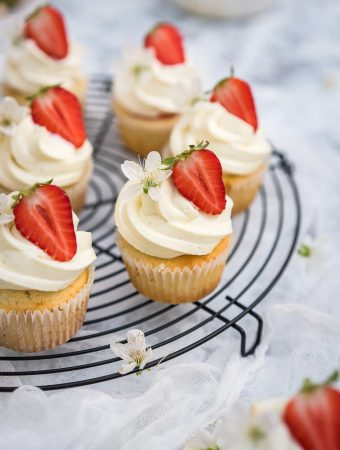 Strawberry filled cupcakes with a white chocolate whipped ganache swirl on a black round wire rack