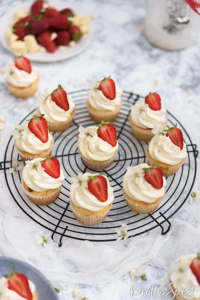 white cupcakes with mascarpone frosting and strawberries on a black round wire rack