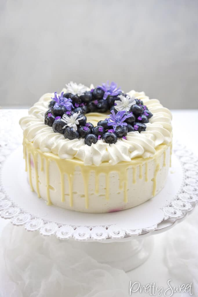A blueberry yogurt mousse cake with white chocolate drip and blueberries on top