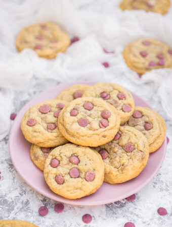 Ruby chocolate chip cookies piled on a pink plate