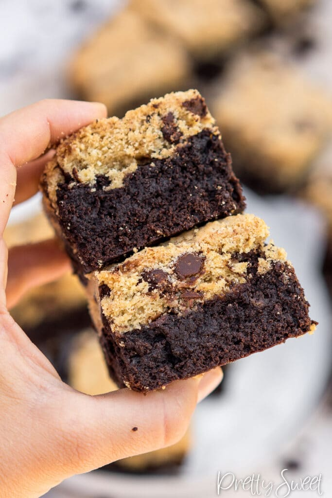two pieces of brownie bars with cookie top up close held in hand