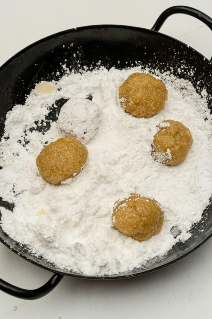 rolling balls of amaretti cookie dough in powdered sugar