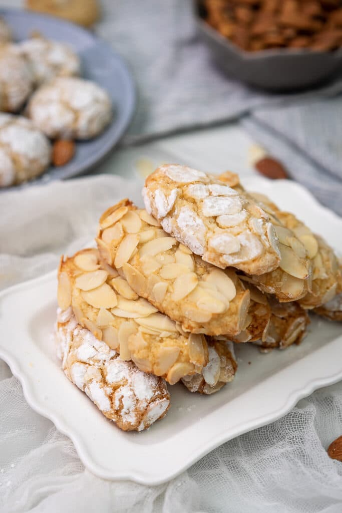 oval shewy almond cookies stacked in a pyramid on a rectangular plate