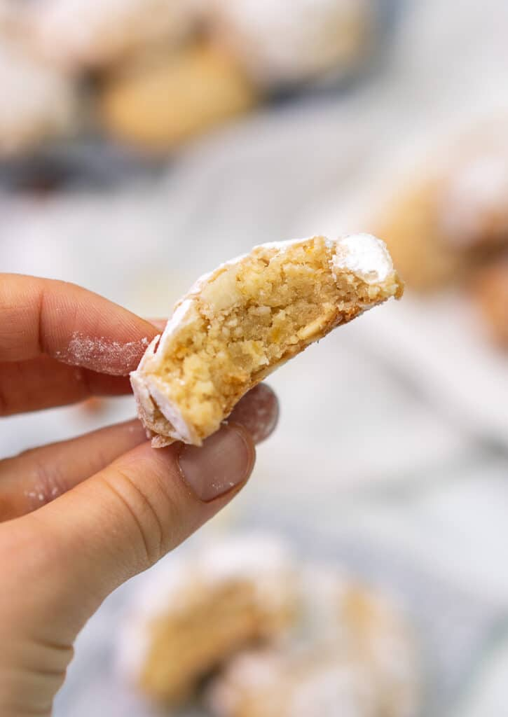 a bitten almond crinckle cookie help in hand up close