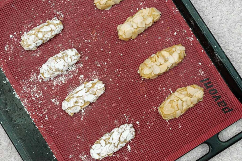 oval almond cookies rolled in slivered almonds laying on a tray