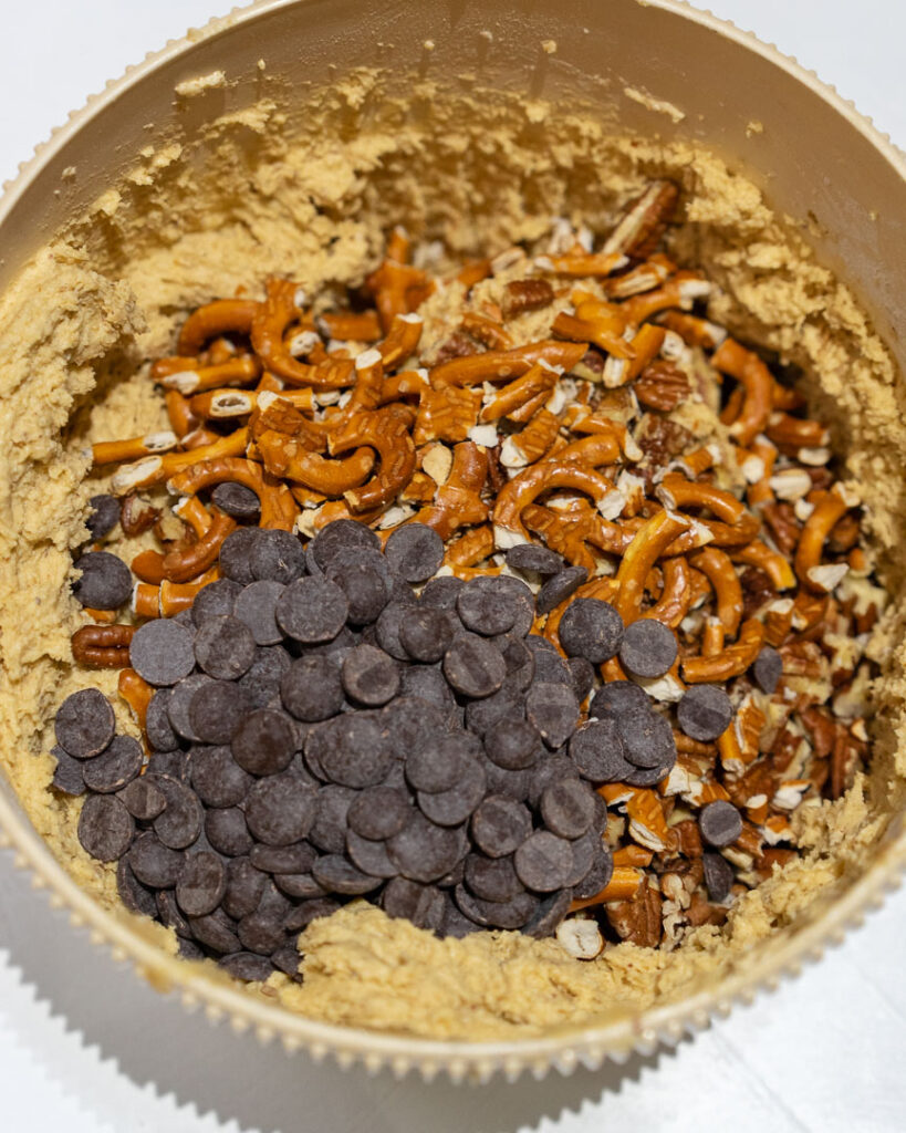 cookie dough with added pretzels, chocolate chip and pecans in a bowl