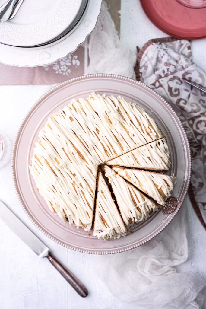 Round frosted Cinnamon Roll Cheesecake from the top on a cake stand with plates and a knife around