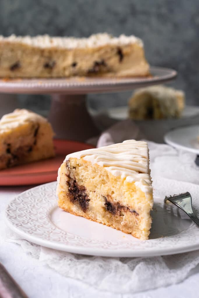 a Cheesecake with cinnamon swirls piec from the side on a white plate with a small fork and a cheesecake on a cake stand in the back