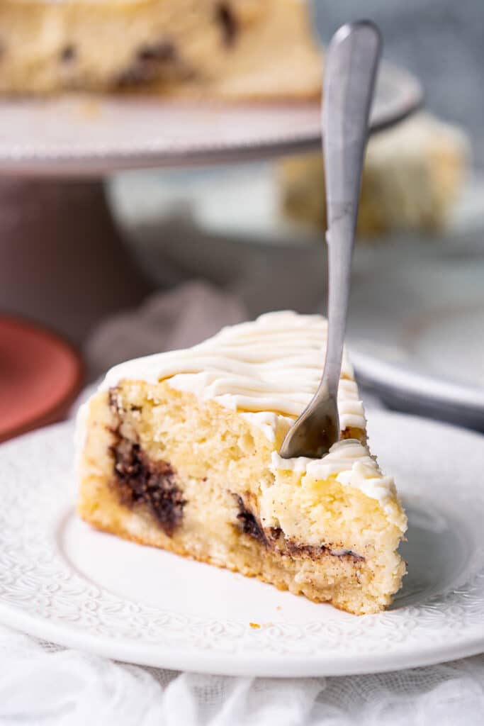 a piece of cinnamon roll cheesecake on a white plate with a fork stabbed into it
