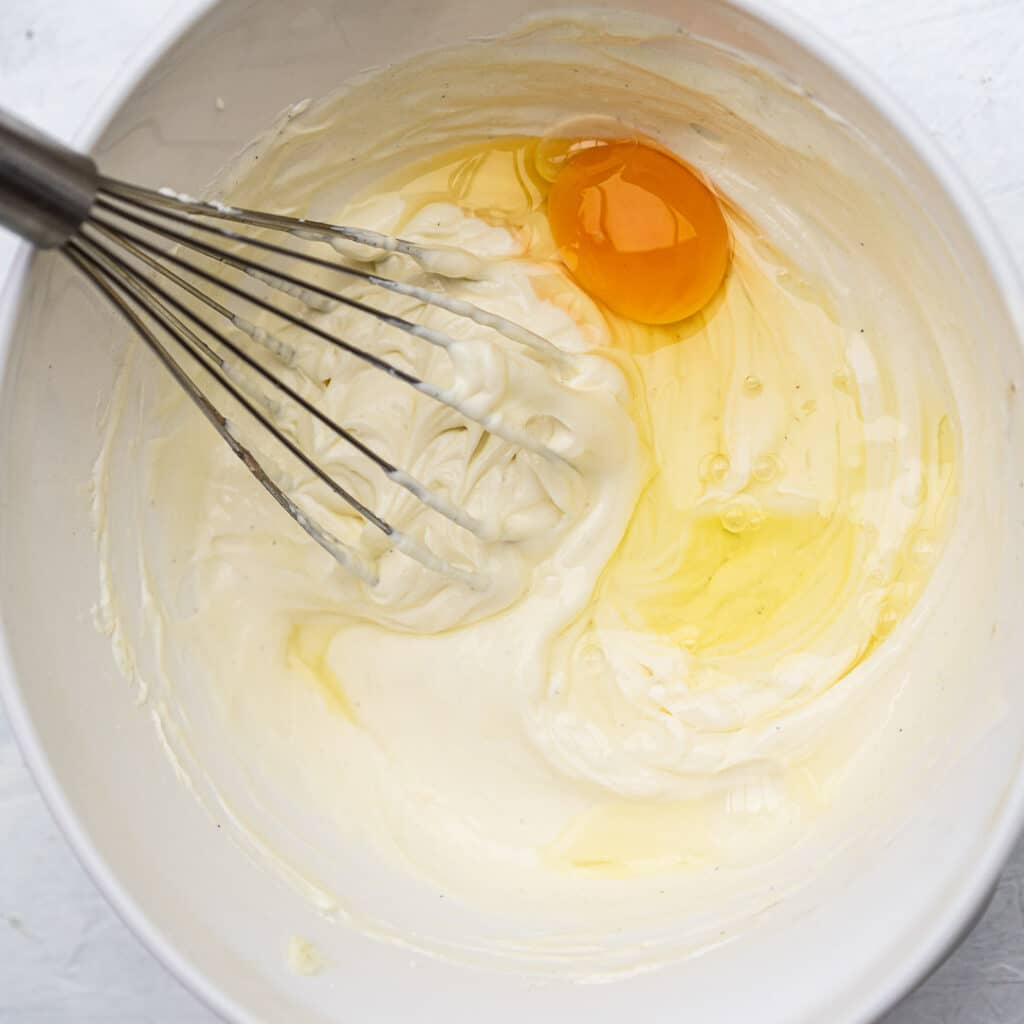 adding eggs to cheesecake batter in a white bowl with a whisk