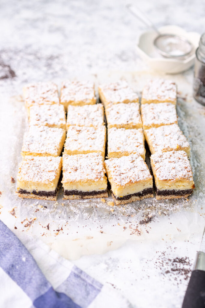 16 poppy seed cheesecake crumble bars on parchment paper