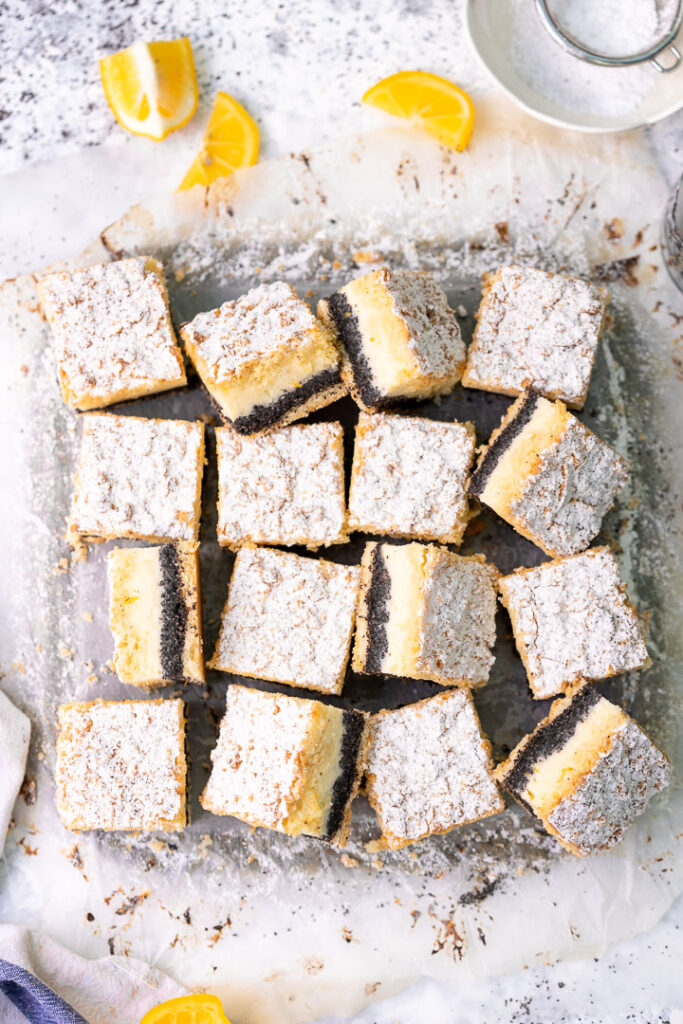 poppy seed lemon cheesecake bars with powdered sugar, facing different directions on parchment paper