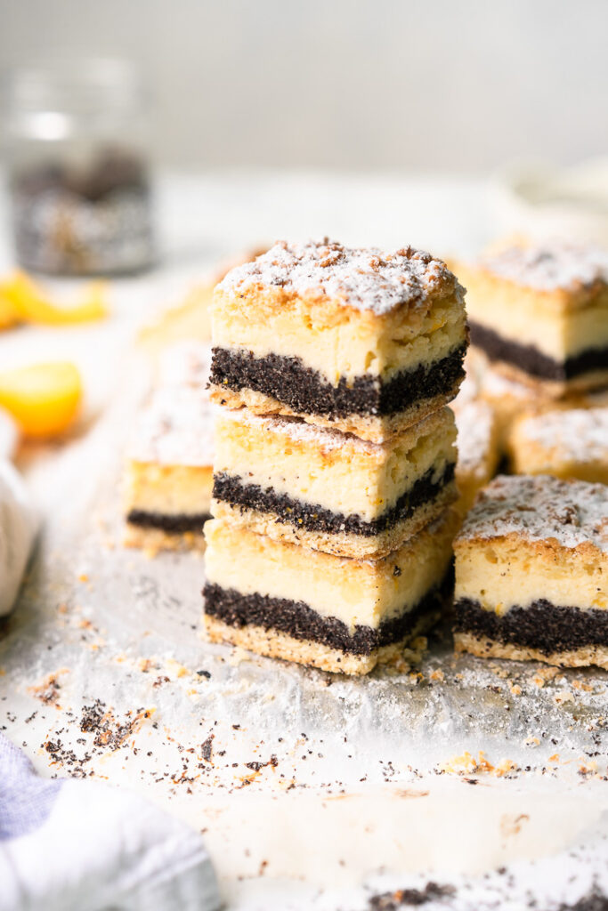 a stack of poppy seed crumble bars with more bars around