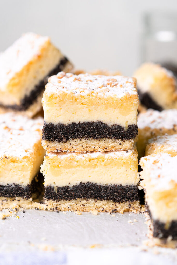 a close up of two cheesecake bars stacked with more bars stacked around