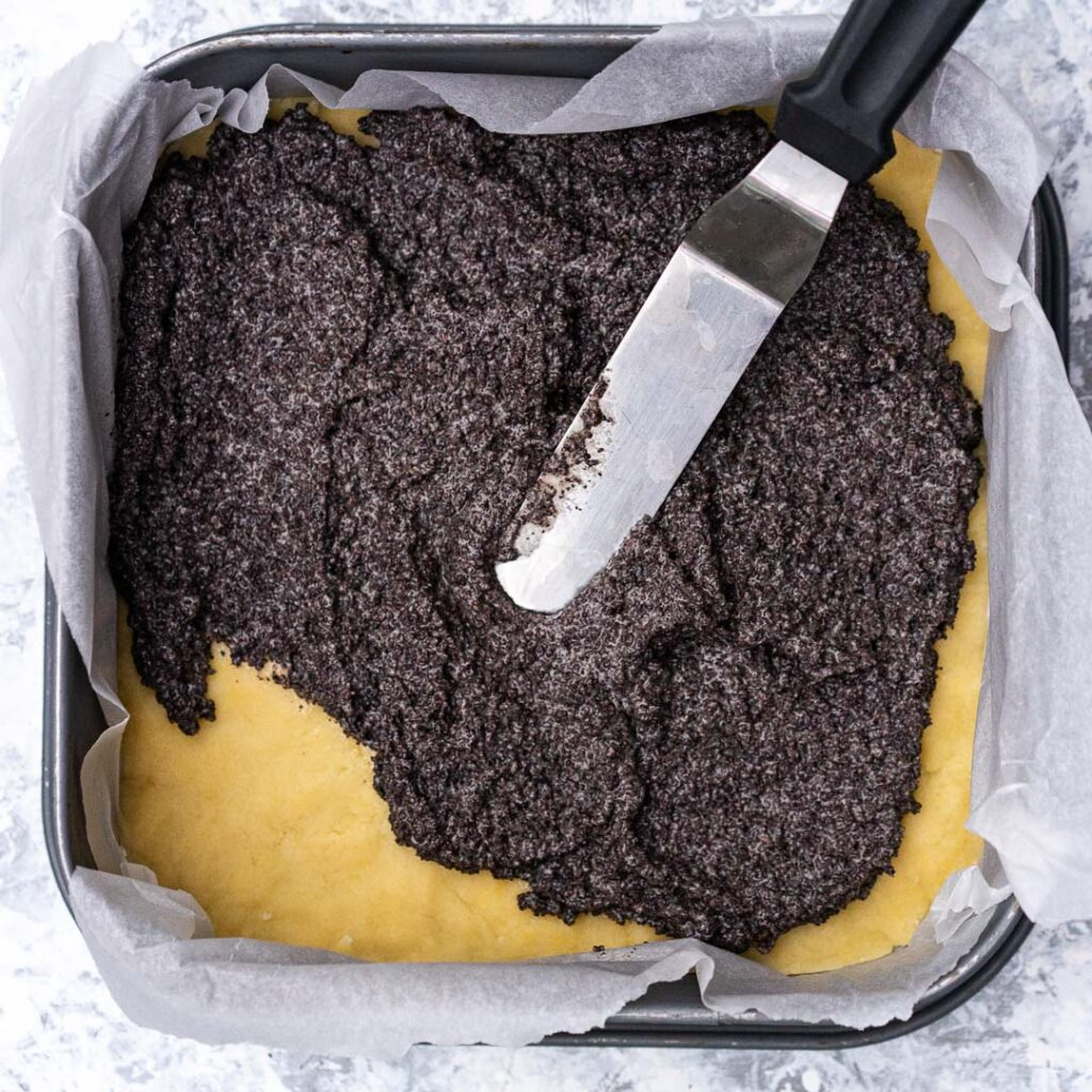 smearing the poppy seed filling on top of the dough in a baking pan