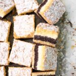 a close up of a poppy seed cheesecake crumble bar from the top with more bars around