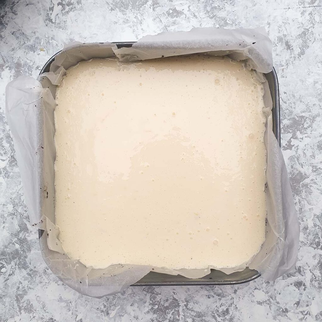 Unbaked cheesecake in a square spring-form pan